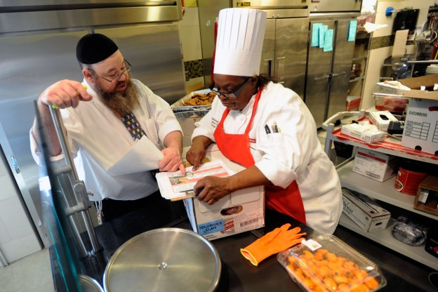 Rabbi Jonathan Powers, the Mashgiach at Muhlenberg College, left, reviews the Kosher luncheon menu with Sous Chef Deborah Noel, right, in the dining Monday, Dec. 7, 2015 in Allentown, Pa. (Bradley C Bower/Philadelphia, PA. )